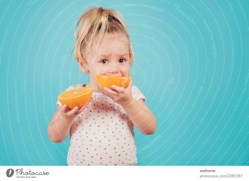 Baby isst eine Orange auf blauem Hintergrund Lebensmittel Frucht Ernährung Essen Mittagessen Lifestyle Freude Gesunde Ernährung Mensch feminin Mädchen Kindheit
