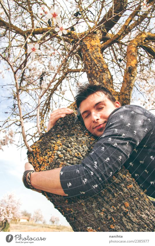 Junger Mann umarmt einen Baum Lifestyle Stil Freude Gesundheit Mensch maskulin Jugendliche Erwachsene 1 30-45 Jahre Umwelt Natur Frühling Schönes Wetter Blume