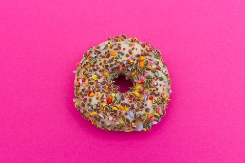 Zuckersüßer Donut auf pinkem Hintegrund Lebensmittel Kuchen Süßwaren Krapfen Essen Duft Glück lecker mehrfarbig rosa Laster Appetit & Hunger genießen Ernährung