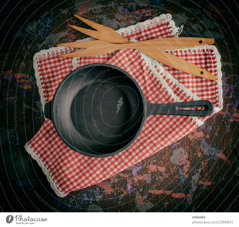 runde leere schwarze gusseiserne Bratpfanne Topf Pfanne Gabel Tisch Küche Holz Metall Stahl alt retro Sauberkeit rot Hintergrund Lebensmittel Kochgeschirr