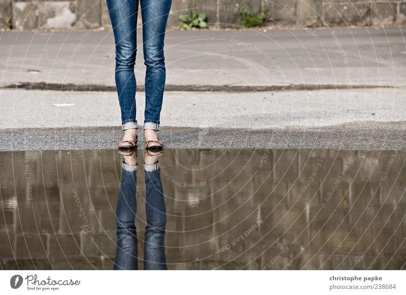 Zwei Mal Ein Zwei-beiner Mensch Wasser feminin Beine Beton paarweise stehen Jeanshose Asphalt Schuhe Wasseroberfläche Pfütze anonym kopflos Bekleidung unerkannt