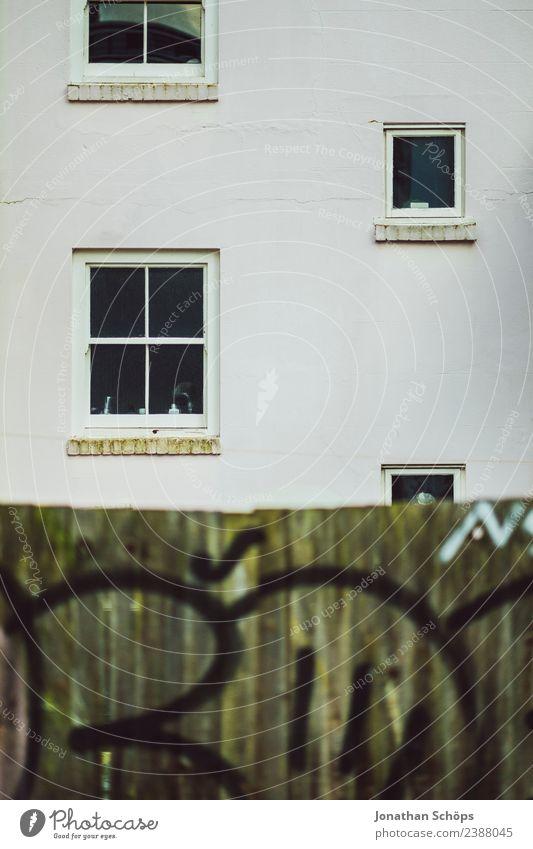 Fassade mit Holzwand in Brighton, England Stadt Stadtrand bevölkert Haus Armut hässlich Architektur Fenster Zaun Holzzaun Graffiti weiß trüb graphisch einfach
