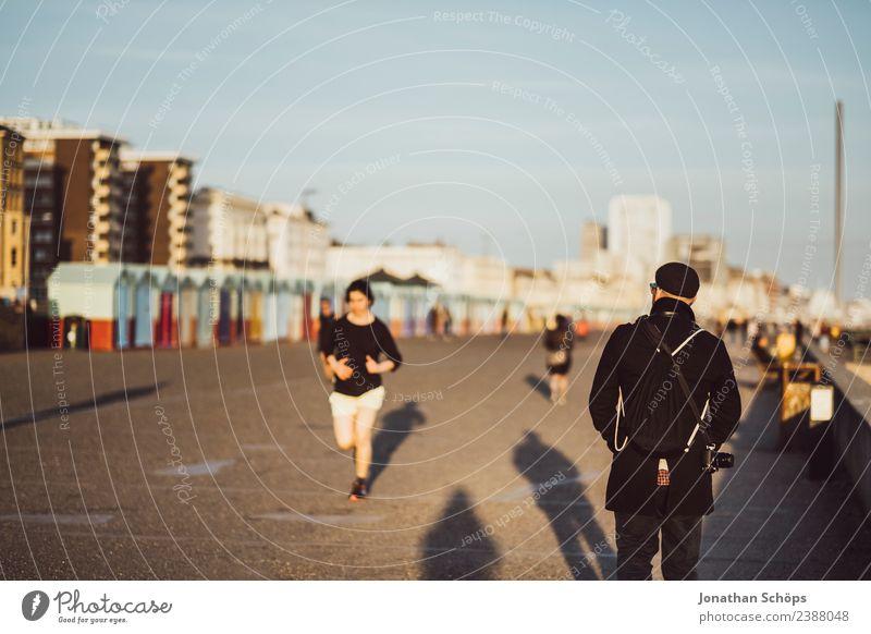 Tourist läuft auf Strandpromenade in der Abendsonne Mensch Ferien & Urlaub & Reisen Jugendliche Junge Frau Stadt Junger Mann Erholung Haus Sport Tourismus