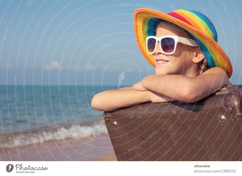 Ein glückliches kleines Mädchen mit Koffer, das am Strand sitzt. Lifestyle Freude Glück Erholung Freizeit & Hobby Spielen Ferien & Urlaub & Reisen Tourismus