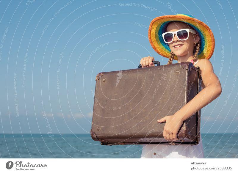 Ein glückliches kleines Mädchen mit Koffer, das am Strand steht. Lifestyle Freude Glück Erholung Freizeit & Hobby Spielen Ferien & Urlaub & Reisen Tourismus