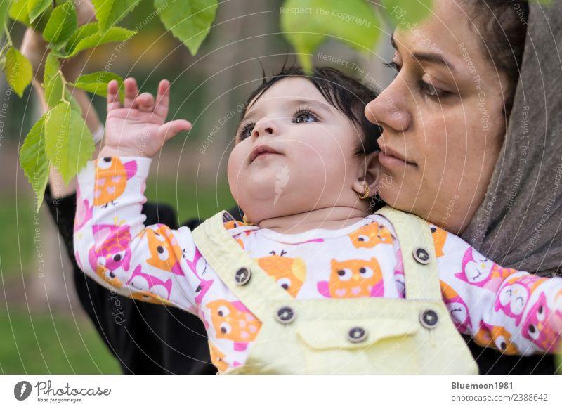 Kleines Baby erforscht und berührt in der Umarmung seiner Mutter neue Frühlingsblätter schön Leben Erholung Kind Mensch Frau Erwachsene Eltern