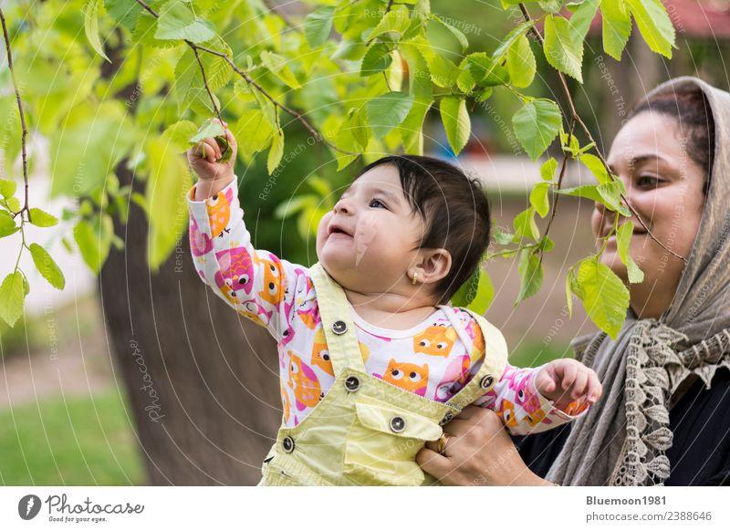Das kleine Baby berührt frische Frühlingsblätter in der Umarmung ihrer Mutter. Lifestyle schön Wellness Leben harmonisch Wohlgefühl ruhig Kindererziehung Mensch