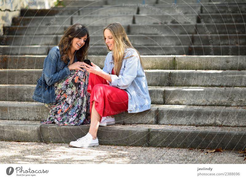 Zwei junge Frauen, die sich ein Smartphone im Freien ansehen. Lifestyle kaufen Freude Glück schön Telefon PDA Technik & Technologie Mensch feminin Junge Frau