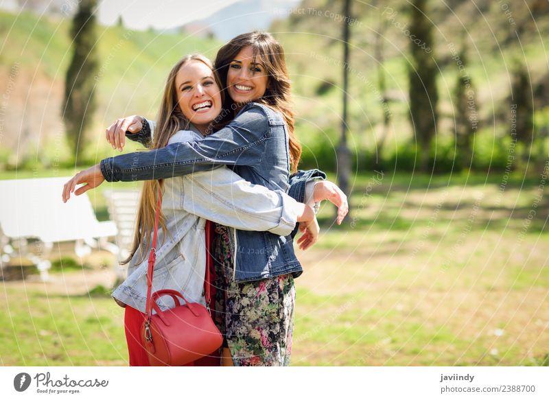 Zwei glückliche Mädchen, die sich im Stadtpark umarmen. Lifestyle Stil Freude Glück schön Mensch feminin Junge Frau Jugendliche Erwachsene Freundschaft 2