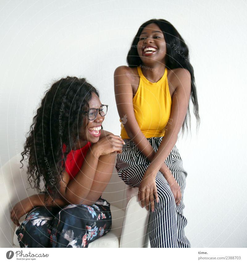 Apolline und Arabella Sessel feminin Frau Erwachsene 2 Mensch T-Shirt Hose Brille schwarzhaarig langhaarig Locken Afro-Look Erholung lachen sitzen Freude