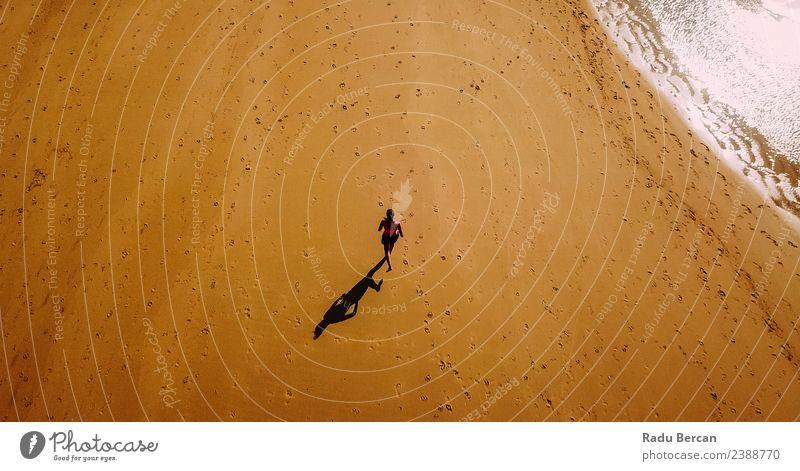Luftaufnahme der sportlichen Frau, die am Strand läuft. Fitness Abenteuer Sommer Meer Sport Sport-Training Sportler Joggen Mensch feminin Junge Frau Jugendliche
