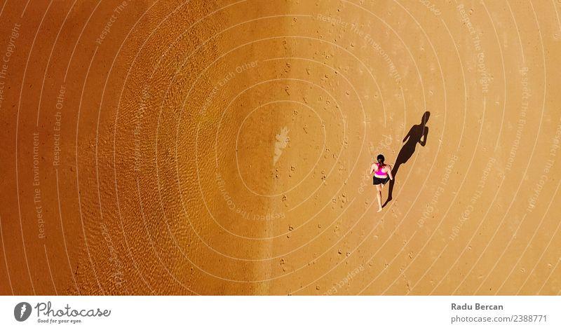 Luftaufnahme der sportlichen Frau, die am Strand läuft. Gesundheit Fitness Leben Abenteuer Sommer Sonne Meer Sport Sport-Training Leichtathletik Sportler Joggen