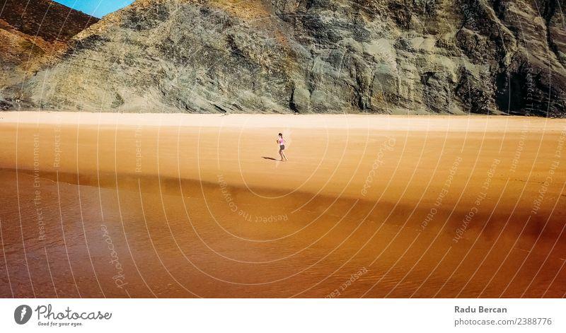Luftaufnahme der sportlichen Frau, die am Strand läuft. Abenteuer Freiheit Sommer Meer Insel Berge u. Gebirge Sport Sportler Joggen Mensch Junge Frau