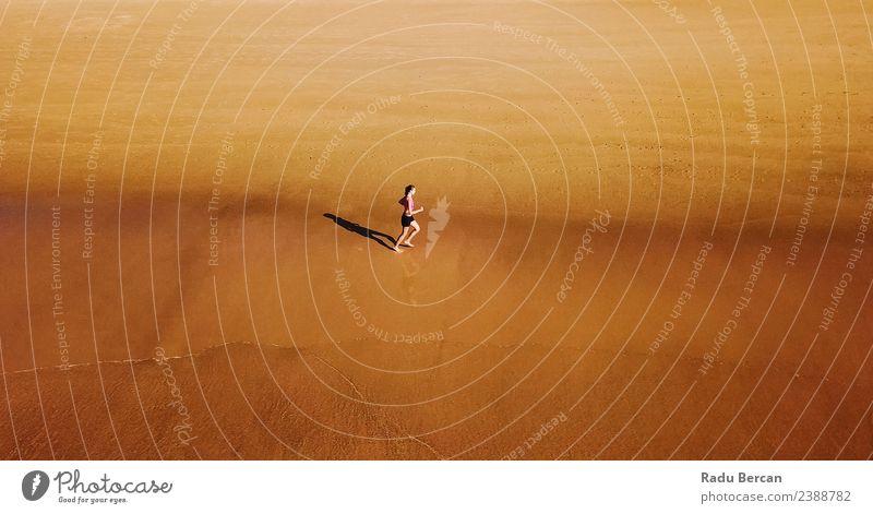 Luftaufnahme der sportlichen Frau, die am Strand läuft. Sommer Sonne Meer Sport Fitness Sport-Training Leichtathletik Joggen Mensch feminin Junge Frau
