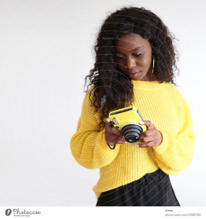Apolline feminin Frau Erwachsene 1 Mensch Rock Pullover Ohrringe brünett langhaarig Locken Fotokamera beobachten festhalten Blick schön gelb Willensstärke