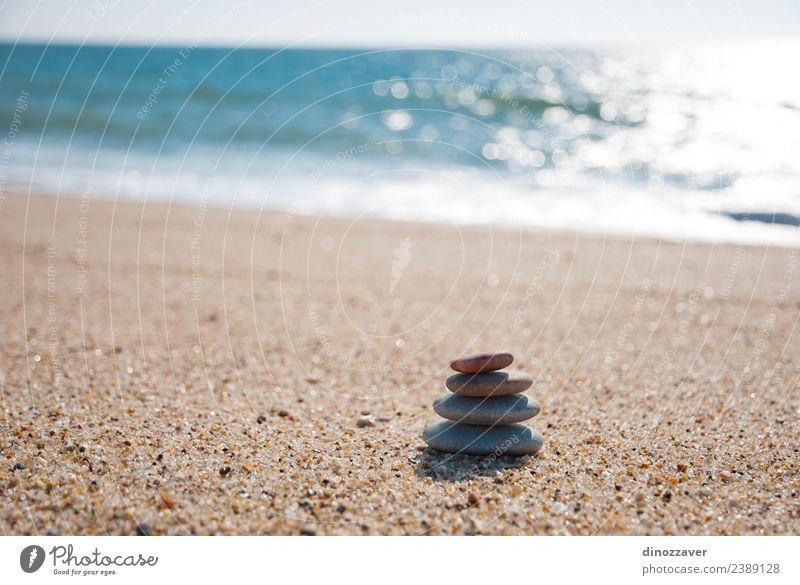 Steine stapeln sich auf dem Sand. Wellness harmonisch Erholung Meditation Spa Sommer Strand Meer Natur Himmel Horizont Felsen Küste natürlich blau schwarz weiß