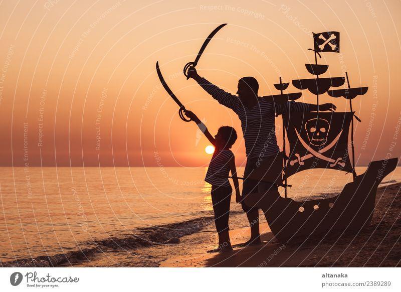 Vater und Sohn spielen am Strand bei Sonnenuntergang. Lifestyle Freude Glück Spielen Ferien & Urlaub & Reisen Ausflug Abenteuer Freiheit Sommer Meer Segeln Kind