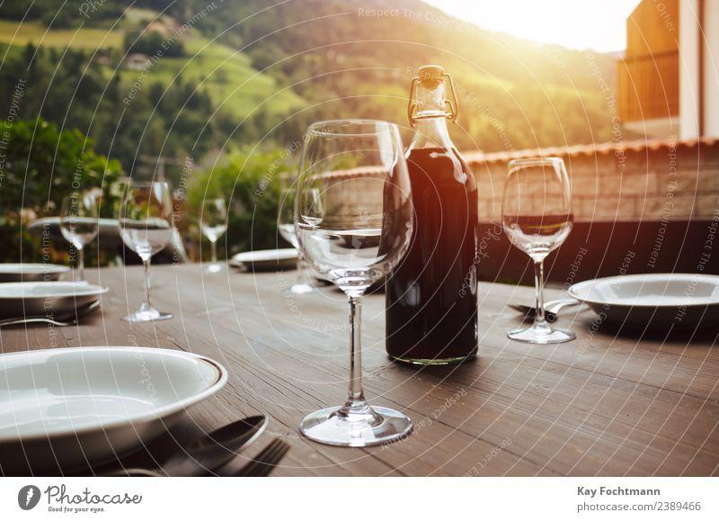 Flasche Rotwein und gedeckter Tisch auf der Veranda Festessen Getränk Alkohol Wein Geschirr Teller Glas Gabel Löffel Lifestyle Reichtum elegant Stil Leben