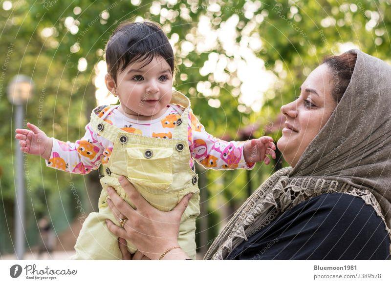 Muslimische Mutter hält ein kleines Baby mit den Armen im Außenbereich. Lifestyle Freude schön Gesundheit Leben Sonne Kind Mensch feminin Mädchen Junge Frau