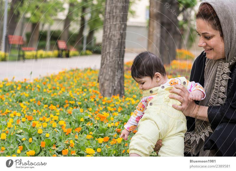 Muslimische Mutter hält kleines Baby in Frühlingsblumen im Park. Lifestyle Freude schön Leben Erholung Spielen Garten Kindererziehung Mensch Mädchen Junge Frau