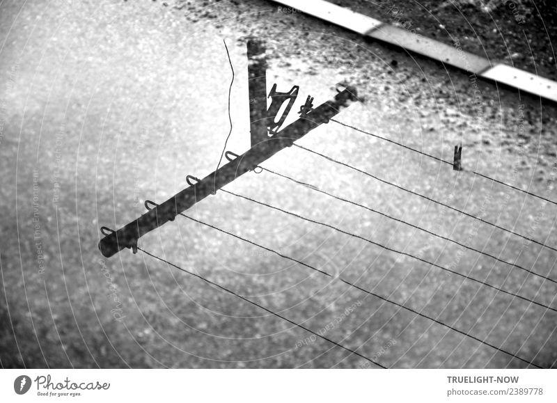 Wäscheleine und -pfahl spiegeln sich in Pfütze auf Weg Garten Erde Wasser Wolken Wetter schlechtes Wetter Regen Stein Sand Metall warten einfach nass retro grau