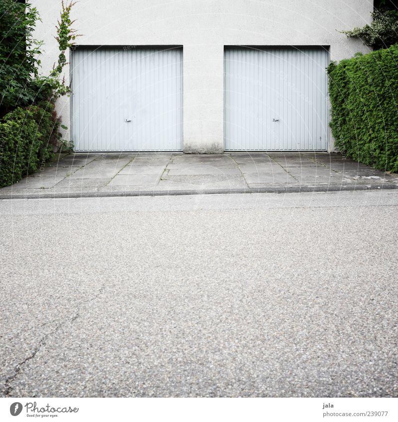 doppelgarage Pflanze Sträucher Grünpflanze Haus Bauwerk Gebäude Architektur Mauer Wand Fassade Garage Straße Bürgersteig trist Farbfoto Außenaufnahme