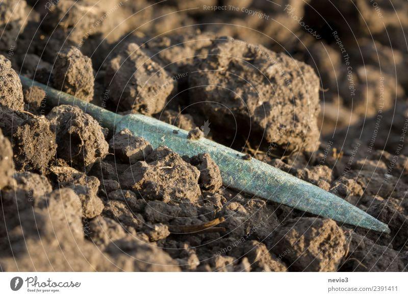 Skythische Pfeilspitze auf frisch bearbeitetem Feld alt nah braun türkis Krieg Krieger Pfeile skythisch Skythen Schatzfund Fundstück Ackerboden Erde Boden