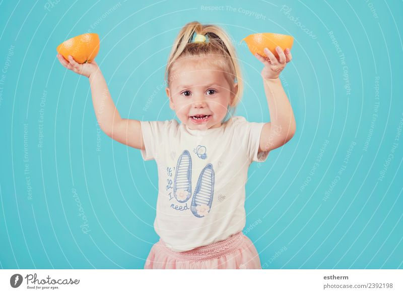 lächelndes Baby mit einer Orange auf blauem Hintergrund Lebensmittel Frucht Ernährung Essen Mittagessen Lifestyle Freude Gesunde Ernährung Mensch feminin