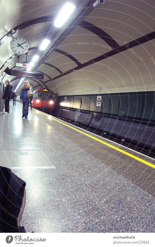 London Underground 3 U-Bahn Bahnsteig Neonlicht Licht Uhr unterwegs Verkehr einfahrender Zug Mensch Platform Passagier