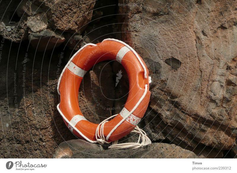 oranger Rettungsring vor Felsen braun weiß Rettungsgeräte Seil Überleben Kreis rund Menschenleer Felswand 1 Farbfoto Außenaufnahme Textfreiraum links