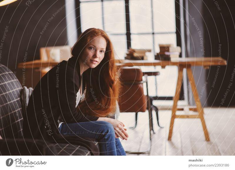 junge Lesekopf-Frau, die sich zu Hause entspannt. Tee Lifestyle Erholung stricken Stuhl Tisch Erwachsene Herbst Wärme Pullover rothaarig Holz Metall träumen