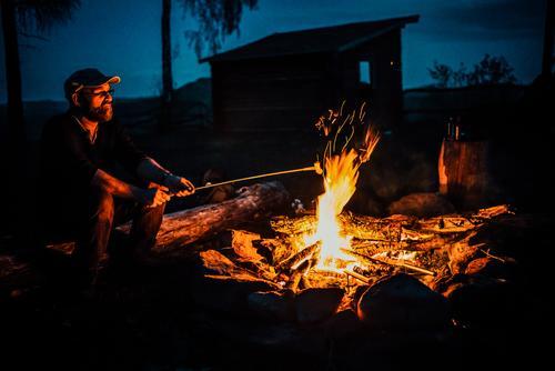 Lagerfeuer Wurstwaren Abenteuer Freiheit Expedition Camping Sommer maskulin Mann Erwachsene Gesicht 1 Mensch Natur Mütze beobachten sitzen Einsamkeit