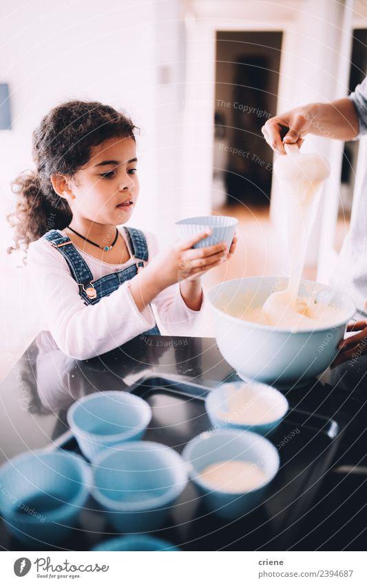 kleines afrikanisches Mädchen macht Muffins in der Küche. Dessert Schalen & Schüsseln Lifestyle Glück Kind Schule Frau Erwachsene Essen zubereiten backen