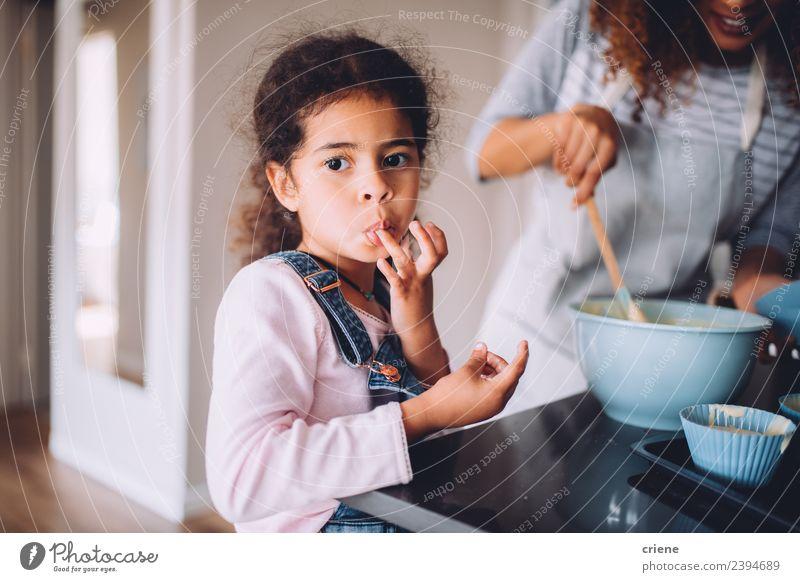 Das kleine afrikanische Mädchen leckt den Teig von den Fingern. Dessert Freude Glück schön Küche Kind Mensch Frau Erwachsene Mutter Kindheit Zusammensein lecker