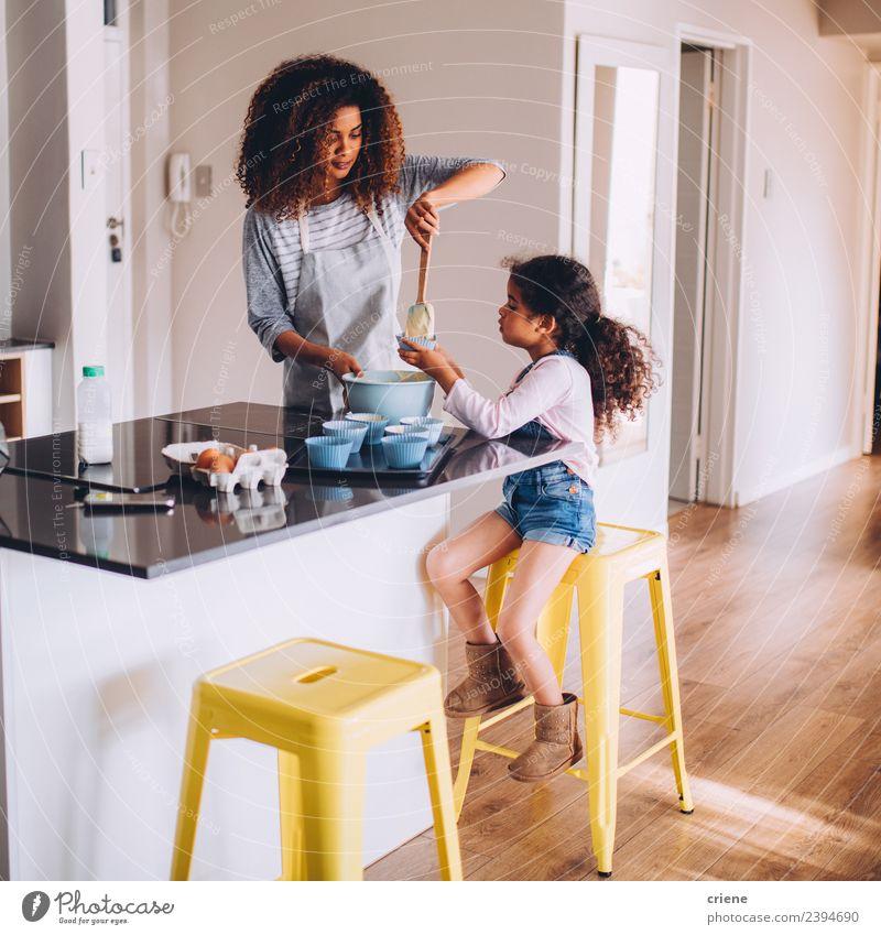 Das kleine afrikanische Mädchen hilft ihrer Mutter bei der Zubereitung von Cupcake-Teig. Teigwaren Backwaren Dessert Freude Glück schön Küche Kind Schule Mensch