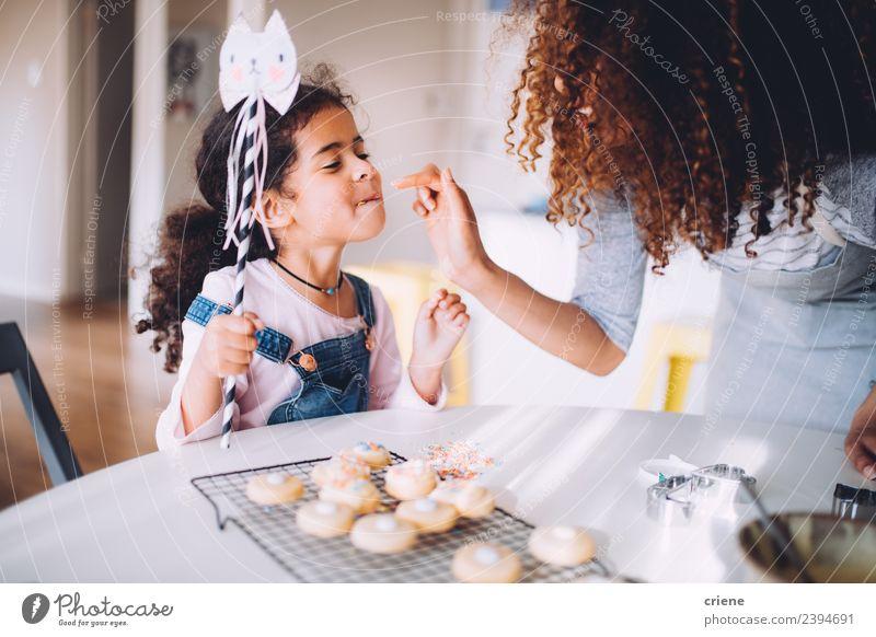 Afrikanische Mutter und Tochter genießen ihre selbstgemachten Kekse. Dessert Freude Glück schön Küche Kind Mensch Frau Erwachsene Kindheit Finger Fröhlichkeit