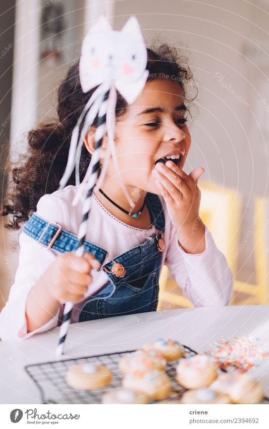 afrikanisches kleines Mädchen isst zu Hause selbstgemachte Kekse. Dessert Lifestyle Freude Glück schön Tisch Küche Kind Mensch Frau Erwachsene Kindheit Lächeln