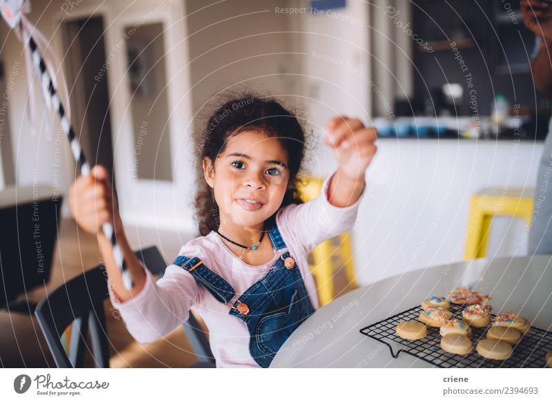 fröhliches afrikanisches Mädchen am Küchentisch sitzend mit gebackenen Keksen Dessert Lifestyle Freude Glück schön Kind Mensch Frau Erwachsene Kindheit Lächeln