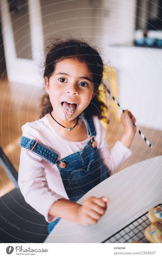 afrikanisches junges Mädchen streckt die Zunge aus und isst dabei Süßigkeiten. Dessert Lifestyle Freude Glück schön Tisch Küche Kind Mensch Frau Erwachsene