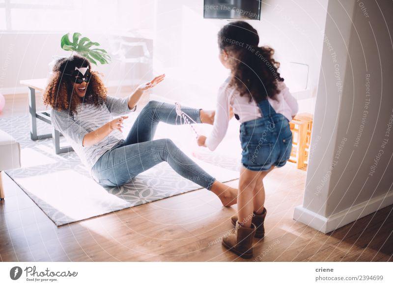 Mutter und Tochter spielen im Wohnzimmer mit Kostümen Freude Glück Spielen Kind Eltern Erwachsene Familie & Verwandtschaft Kindheit lachen Fröhlichkeit