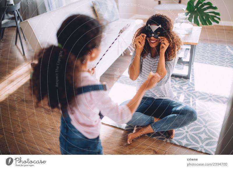 Mutter und Tochter beim Spaß mit Katzenkostüm im Wohnzimmer Freude Glück Spielen Kind Eltern Erwachsene Familie & Verwandtschaft Kindheit lachen Fröhlichkeit