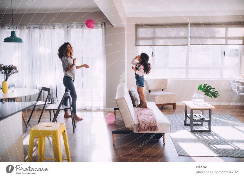 afrikanische Mutter und Tochter beim Spielen mit dem Ballon im Wohnzimmer Glück Dekoration & Verzierung Kind Frau Erwachsene Familie & Verwandtschaft Kindheit