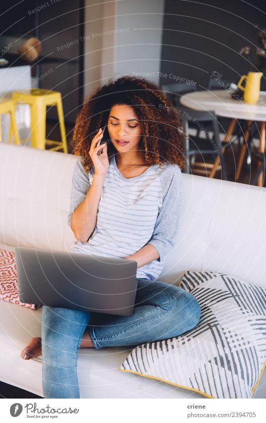 afrikanische Frau auf ihrem Handy beim Blick auf den Laptop Arbeit & Erwerbstätigkeit Business sprechen Telefon Computer Notebook Mensch Erwachsene Lächeln