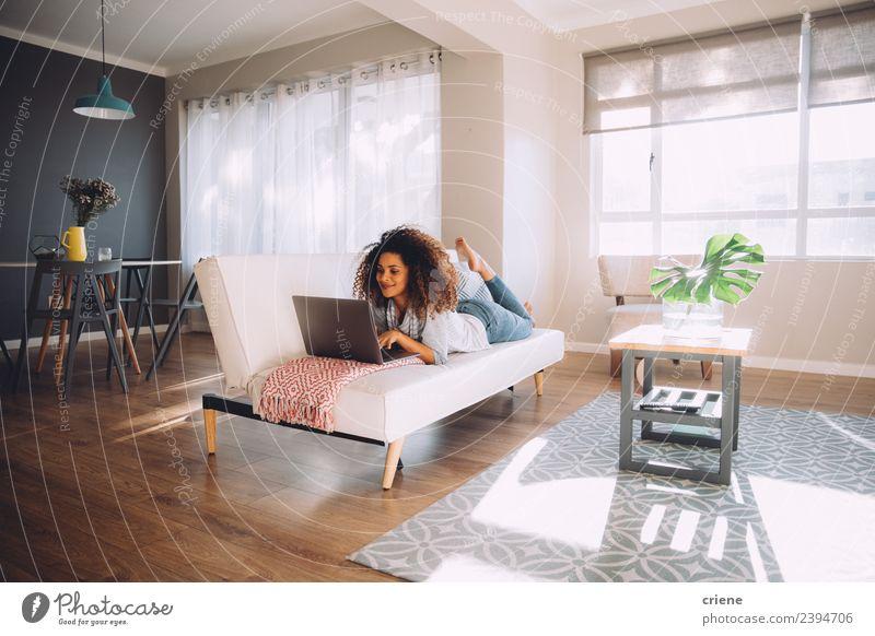 afrikanische glückliche Frau auf der Couch liegend mit Laptop Lifestyle Glück schön Erholung Sofa Arbeit & Erwerbstätigkeit Computer Notebook