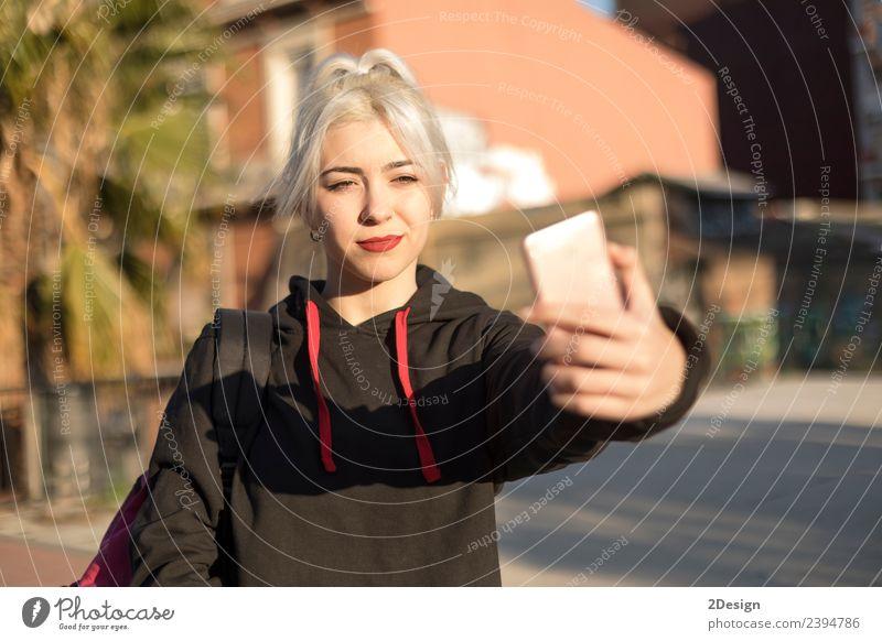 Junge Frau nimmt Selfie nach der Schule. Lifestyle Stil Freude Glück Erholung Berge u. Gebirge Schulhof Schulkind Schüler Telefon Handy PDA Fotokamera Mensch