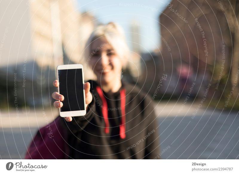 Vorderansicht eines glücklichen Mädchens mit einem leeren Smartphone-Display. kaufen Spielen Bildung Schulkind Schüler Telefon Handy MP3-Player PDA Mensch