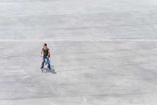 Junger Mann steht mit seinem Fahrrad auf einem Platz. Lifestyle Leben Ferien & Urlaub & Reisen Tourismus Mensch maskulin Jugendliche Erwachsene 1 30-45 Jahre