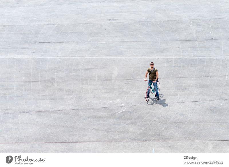 Junger Mann steht mit seinem Fahrrad auf einem Platz. Lifestyle Leben Ferien & Urlaub & Reisen Tourismus Sommerurlaub Mensch maskulin Jugendliche Erwachsene 1