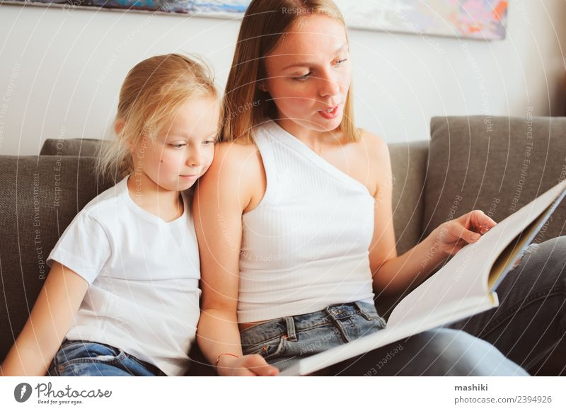 Mutter liest der Tochter ein Buch vor. Lifestyle Freude Erholung Spielen lesen Schlafzimmer Kleinkind Eltern Erwachsene Familie & Verwandtschaft Lächeln