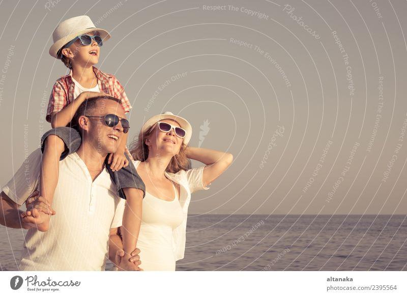 Glückliche Familie steht am Strand am Tag. Menschen, die Spaß im Freien. Konzept der Sommerurlaub und freundliche Familie. Lifestyle Freude Leben Erholung